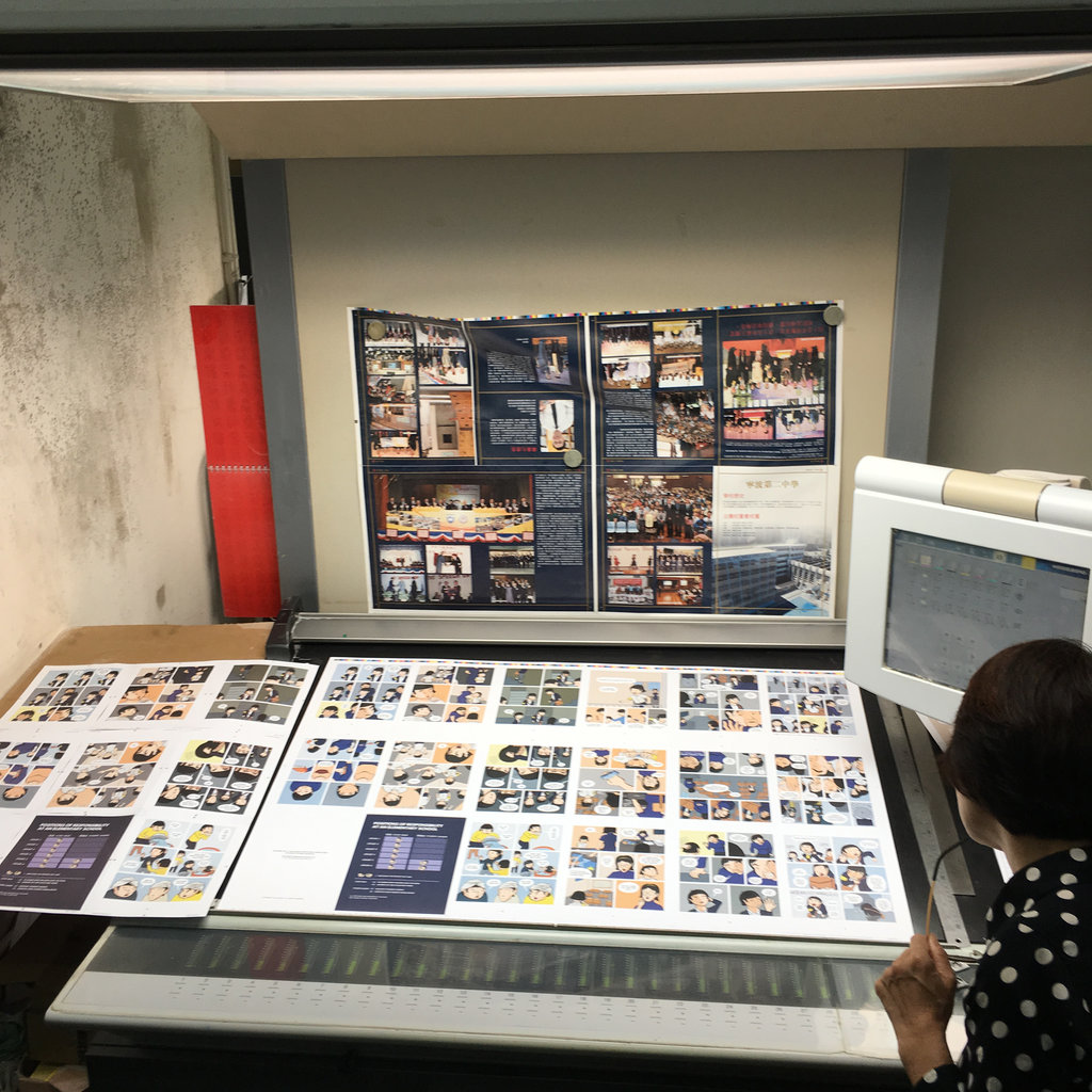 Photo of a woman looking at a large spread of various pages laid out on a big table sloping up before they're cut